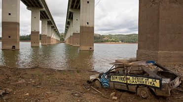 "The frame of a car with a text that reads in Portuguese ""Welcome to the desert of Cantareira,"" written on its side, is revealed by the receding waters of the Atibainha reservoir, part of the Cantareira System that provides water to the Sao Paulo metropolitan area, in Nazare Paulista, Brazil, Thursday, Jan. 29, 2015. The southeastern Brazil is suffering the worst drought in more than eight decades and authorities put Sao Paulo in a state of alarm when the water utility director said that rationing could be implemented in a dramatic five days-off, two days-on. (AP Photo/Andre Penner)"